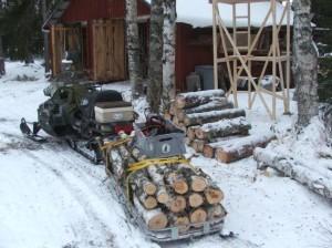 Brænde hentes i skoven m snescooter.
